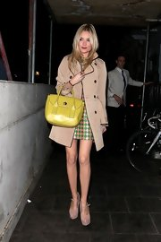 Laura Whitmore teamed nude platform Mary Janes with a trenchcoat and a print dress for a night of partying.