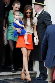 Victoria Beckham balanced Harper on one hip in a bright orange mini and platform sandals.