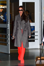 Victoria Beckham was spotted at JFK Airport looking fall-chic in a plaid coat and bright red slacks, both from her own line.