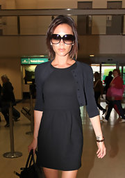 Victoria Beckham wore a dainty cropped cardigan over her LBD at the Heathrow Airport.