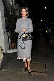 Alexa Chung bundles up in a long gray evening coat with button detailing along the sleeves and waist.
