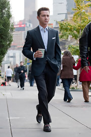 Shia LaBeouf looked dapper in black slacks, a navy jacket, and Gucci loafers on the set of 'Wall Street 2.'