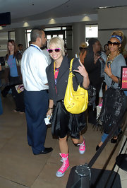 Kimberly showed off her bright and bold style while traveling through the airport. She topped her hot pink shoes and sunglasses off with a bold yellow studded shoulder bag.