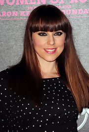 Melanie wears her hair in a long straight style with front bangs.