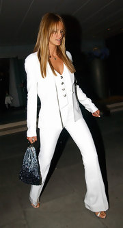 Elle Macpherson showed off her lithe, rockstar frame in a sharp white suit and vest with metallic strappy sandals.