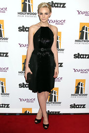 Carey Mulligan finished off her sultry LBD with a glossy black studded knot clutch.