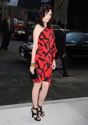 Coco Rocha accented her stunning red and black graphic print dress with a sleek black snakeskin clutch.