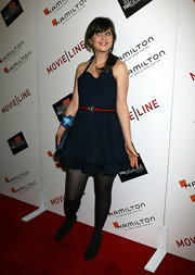 By belting her blue halter dress with this simple red belt, Zooey adds some color and a waistline to her ensemble.