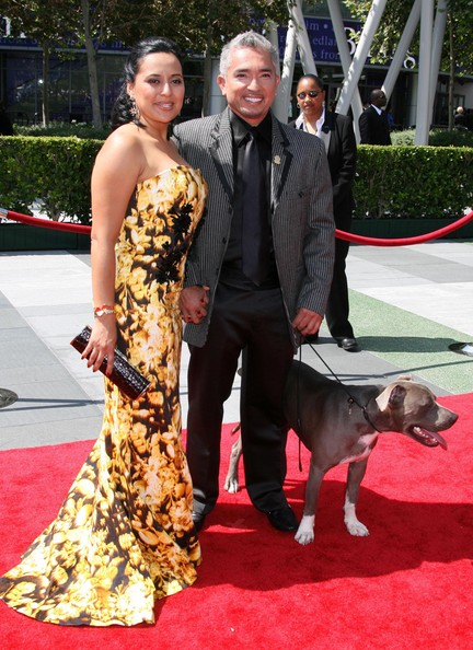 Cesar wears a pinstripe suit jacket with a black bordered collar and lapel to accompany his all black ensemble--and his cute dog!