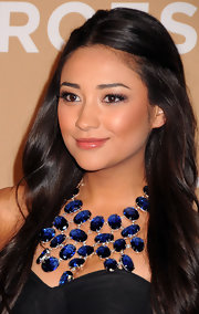 Shay Mitchell wore a sapphire blue statement necklace with her bare neckline.