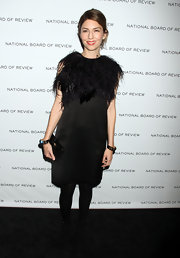 Sofia is famous for her fabulous minimalist style. Here she dons a little black dress with a feathered neckline.