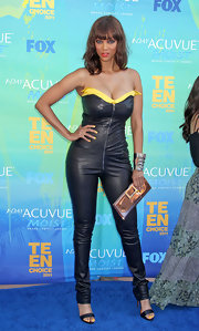 To make her catsuit even more interesting, Tyra carried this metallic bronze clutch.