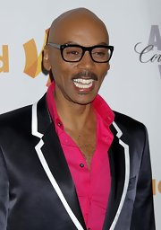 RuPaul showed off his classic shades which he paired with a bright pink shirt and navy blazer.
