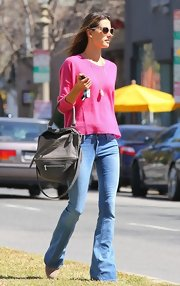 Alessandra Ambrosio dressed super casually in a pair of light flare jeans and a pink sweater.