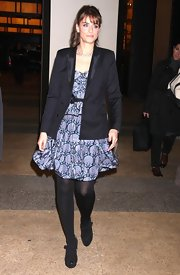 Amanda dons a long navy blazer with satin lapels over a flowing print dress and black tights.
