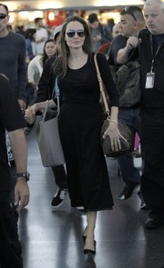 Angelina Jolie kept it understated in a black wrap dress during a flight to New York City.