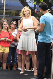 Anne Heche accessorized her fun white frock with classic nude peep toe pumps.