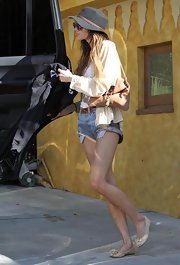 Ashlee Simpson paired her cut off shorts with a brown leather shoulder bag.