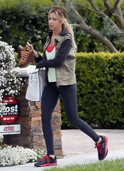 Ashley Tisdale traded in her typical feminine frocks for a more casual and cool look with this zip-up hoodie with a funky vest.