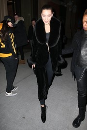 Bella Hadid complemented her coat with black patent ankle boots by Giuseppe Zanotti.