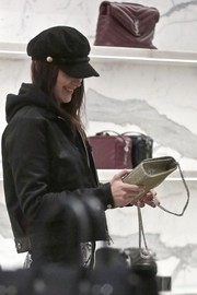 Bella Hadid accessorized with a black military cap while shopping at Saint Laurent.