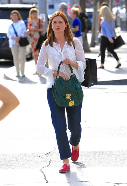 Bonnie Wright pulled her look together with a green suede hobo bag.