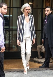 Cara Delevingne headed out in New York City looking impeccable in a striped blazer by Brunello Cucinelli layered over a white silk cami.