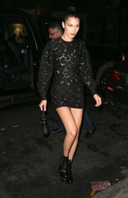 Bella Hadid toughened up her dress with black platform ankle boots, also by Versace.