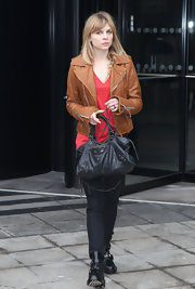 Clemence Poesy kept things chic with an edge, carrying a distressed black leather tote.
