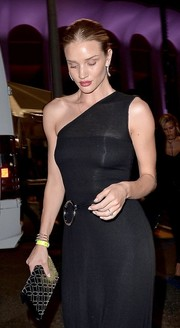 Rosie Huntington-Whiteley paired a studded black clutch by Alaia with a one-shoulder dress for her look during Rihanna's concert.