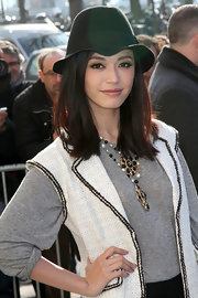 Fan dons a menswear inspired hat with her eclectic ensemble at the Chanel fashion show in Paris.