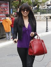 Cheryl Burke brightened up her look with a vibrant red tote with studded trim.