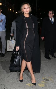 Chrissy Teigen finished off her dress with a chic black wool coat.