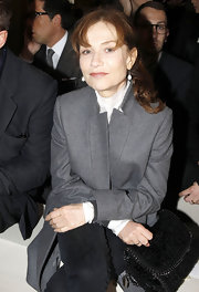 Isabelle Huppert mixed menswear-inspired with ultra-feminine at the Stella McCartney fashion show, wearing a gray wool coat and accessorizing with a textured black velvet purse.