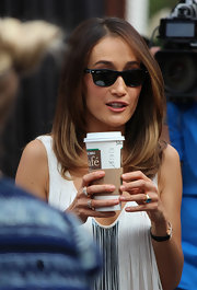 Maggie Q hid behind a pair of Ray-Ban wayfarers during a visit to 'Extra.'