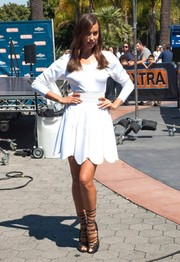 Irina Shayk showed off her tanned and toned pins in a little white dress with a scalloped hem during her appearance on 'Extra.'
