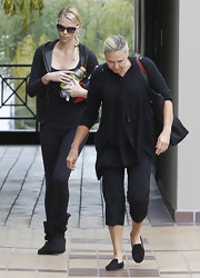 Charlize was comfy in black leggings and black flat boots.