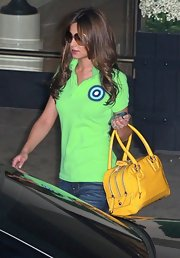 "Cheryl toted the virant yellow leather ""Metallic Lily Bag"" with a green polo shirt, jeans and heels. The multi-zippered handbag is spacious and stylish- perfect for the traveling popstar."