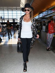 Chrissy Teigen departed on a flight a LAX wearing a lightweight print coat over a tank top and leggings.
