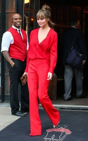 Chrissy Teigen matched her blouse with red pants by Victoria Beckham.