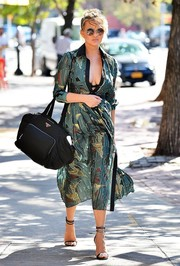 Chrissy Teigen was a head turner on the streets of New York City in a semi-sheer teal shirtdress, which she left partially unbuttoned to reveal her cleavage.