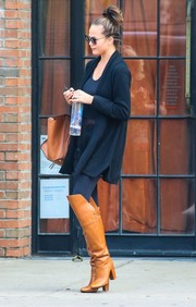 Chrissy Teigen was spotted in NYC looking chic in a navy wool coat and tan knee-high boots.