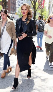 Chrissy Teigen took a stroll in New York City looking edgy in black Givenchy open-toe ankle boots, a leather jacket, and a double-slit dress.