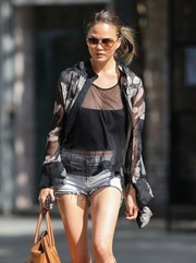 Chrissy Teigen layered a printed button-down over a sheer top and denim cutoffs for a day out in New York City.