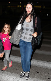 Courteney Cox dressed down her travel attire with gray and black sneakers.