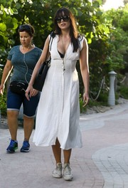 Daisy Lowe headed to the beach wearing a low-cut, button-front white dress.