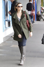 Dannii Minogue showed her more casual side in a pair of gray knee high boots. She paired the leather boots with an olive military inspired jacket and festive red purse.