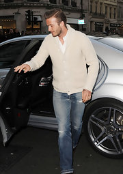 David Beckham looked dapper as ever in a preppy cream cardigan and distressed denim.