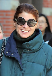 Debra Messing smiled in a pair of round black oversize sunglasses.