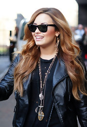 Demi Lovato left a studio in London wearing her hair in long coppery layers featuring smooth loose waves.